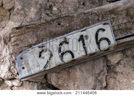 Old vehicle license plate in a old house in Spain