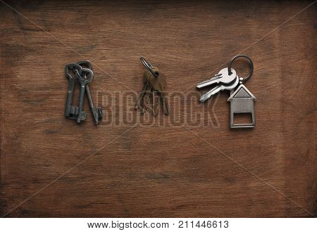 Three bunches of keys. New steel and brass keys on keyrings with house shaped trinklet on rustic brown wood. Choice, key to dream, safety and security concept, top view, copy space, flat lay