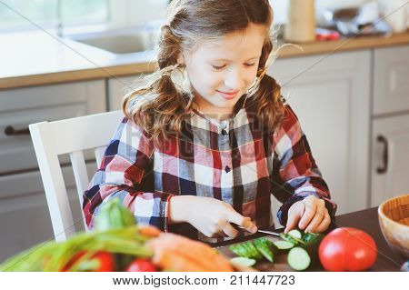child girl helps mom to cook and cut fresh vegetables for salad with knife. Kids learning house work on farm on summer vacations