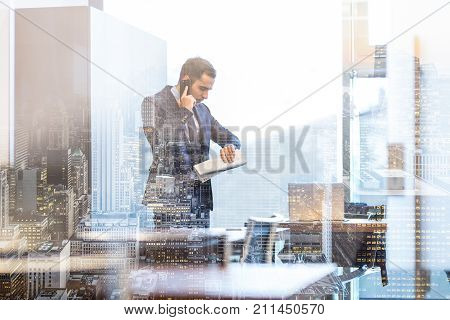 Businessman in modern corporate office, holding financial newspaper, talking on a mobile phone while looking what time is it at his wristwatch. Time is money concept.