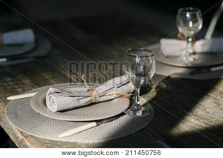 Table setting. Couple empty grey plates. Knife and fork. Old fashioned wine glasses. Rustic napkin. Wooden table. Selective focus.