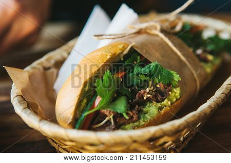 Close-up - sandwich with vegetables and greens and sesame seeds in fresh bun, wrapped in paper and fastened with rope lies in basket on the table