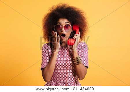 Close-up photo of shocked retro girl with afro hairstyle holding retro phone, looking at camera, isolated over yellow background