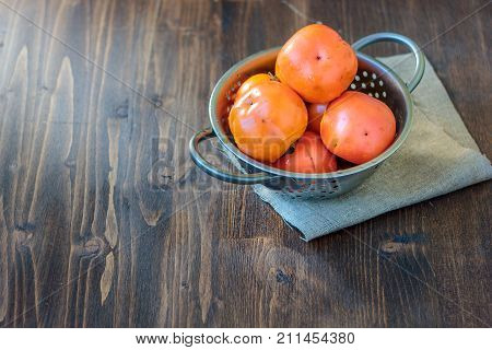 Persimmons in metal collander on wooden table