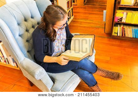 Beautiful Young Girl Sitting in a Chair and Reading a Book