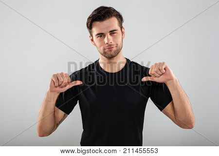 Image of handsome young sports man posing isolated over grey wall background. Looking camera pointing to himself.