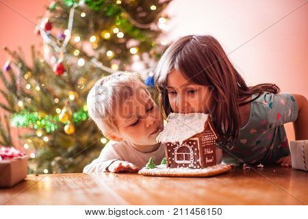 Cute children nibbling a gingerbread cookie house at christmas time