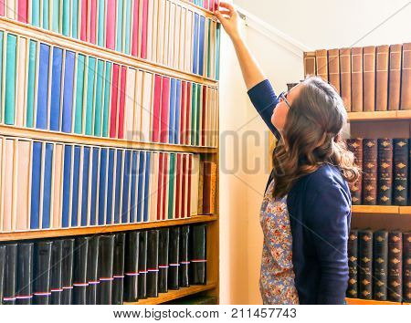 Young Girl Reaching fo a Book on the Bookshelf