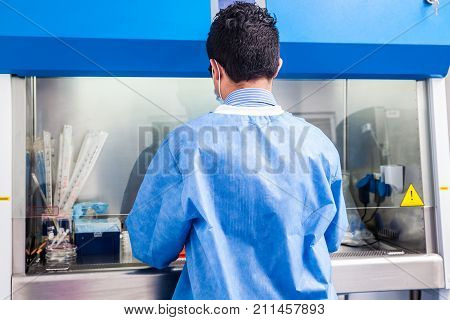 Young Scientist Working In A Safety Laminar Air Flow Cabinet At Laboratory
