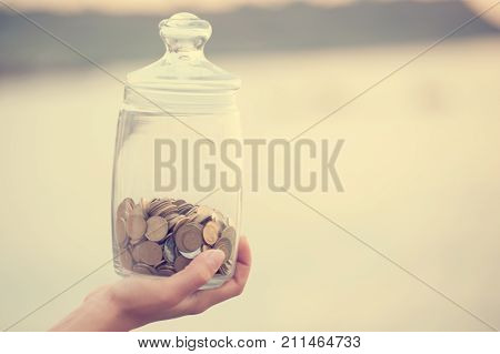 Investment retirement taxes and passive income concept. Coins in a glass jar in hand blur focus. Instagram toned