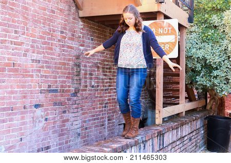 Young Girl Playing and Balancing on Old Red Brick Wall