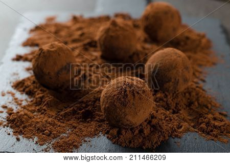 Homemade vegan truffle candies with cocoa powder on a slate plate dark stone background. Selective focus