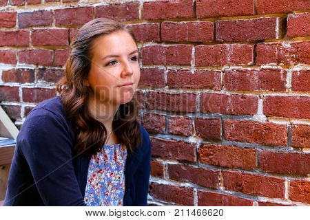 Young Girl Sitting on Stairway Next to an Old Red Brick Wall