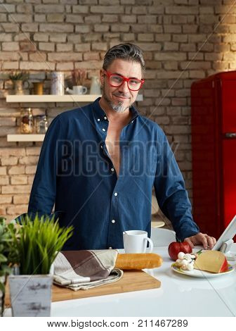 Portrait of an older man. Older man having breakfast in kitchen, happy.
