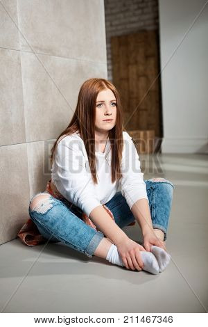 Young ginger-haired girl sitting on floor bored, looking away.
