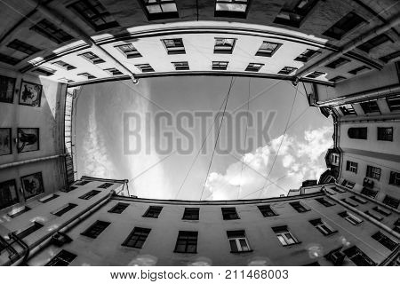Courtyard city look up with fisheye lens effect. Low angle shot of building with windows and cloudy sky background. black and white