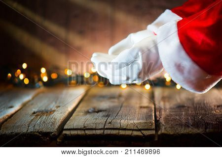 Christmas Santa Claus showing empty copy space on the open hands palm for text. Proposing product. Advertisement gesture presenting point. Holding gift, text or product over wooden background.
