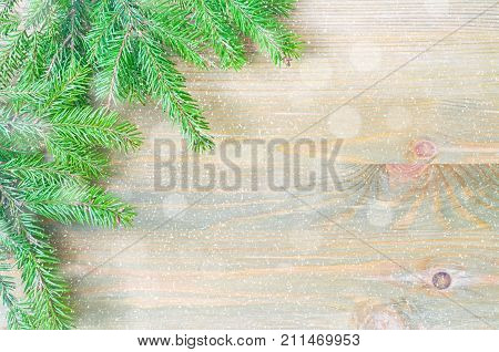 Winter background. Green winter fir tree branches with winter snowflakes on the wooden background. Winter still life with free space for text. Festive winter background, copy space. Winter still life. Winter composition