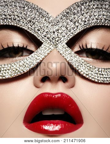 Beautiful Model with Fashion luxe Lips Make-up wearing bright brilliant mask. Masquerade style woman. Holiday celebration look poster