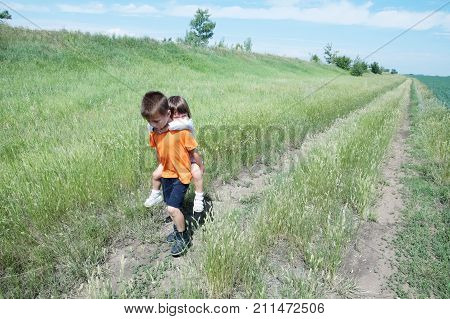Little boy carry little sister on back on the road in the field at summer day