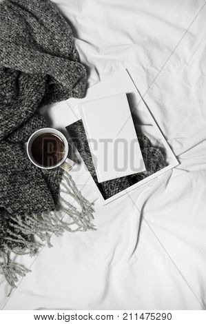 woman's bed top view on a lazy sunday morning in cold weather . Lifestyle with  book, coffee and warm clothes.