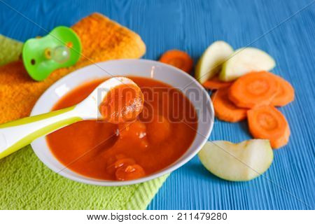 Puree Of Baby Carrot Apple On A Wooden Table Spoon Saucer White Green Pacifier Napkin Orange