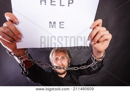 Man With Chained Hands Holding Help Me Sign