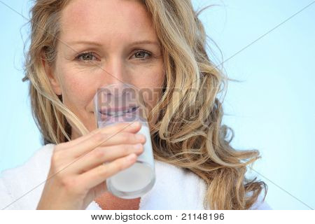 Closeup of woman in bathrobe drinking a glass of milk