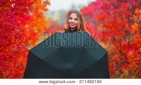 Portrait Of Attractive Young Woman With Umbrella In Autumn