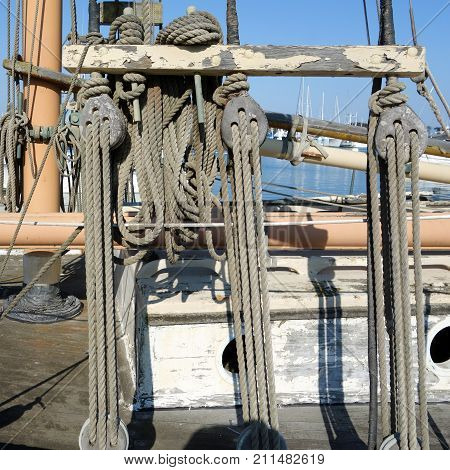 Weathered wooden pulley and ropes mechanical tackle assembly Ventura harbor California