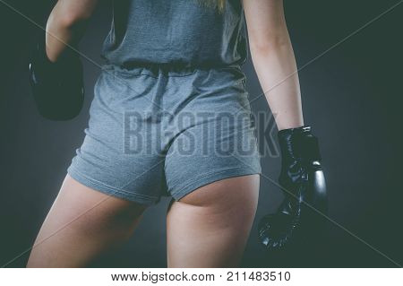 Unrecognizable sporty woman wearing black boxing gloves showing her slim body shape hips curves. Studio shot on dark background.
