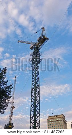 Crane on construction site and the blue sky with clouds