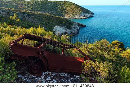 Broken demage rusty car on summer sea coast hill near Arch of San Felice on the Gargano peninsula in Puglia Italy