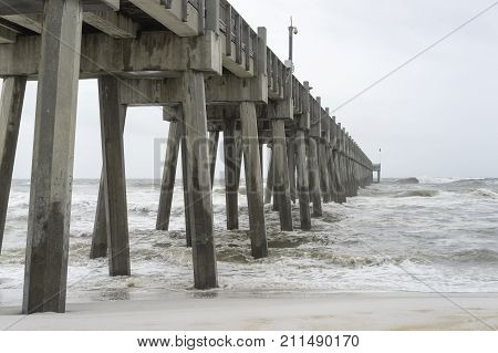 Looking up from the beach at huge concrete fishing pier in Pensacola Florida as tropical storm comes ashore.