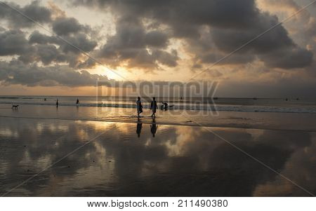 The sunset sky is reflected in the mirror beach of Kuta. The island of Bali. Indonesia.