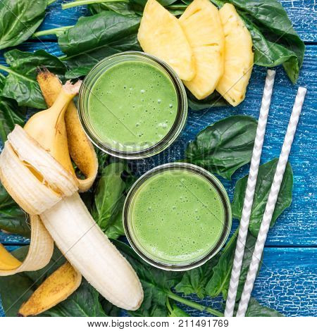Detox green smoothie with spinach pineapple banana and yogurt top view square format