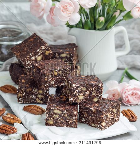 Paleo chocolate energy bars with rolled oats pecan nuts dates chia seeds and coconut flakes square format