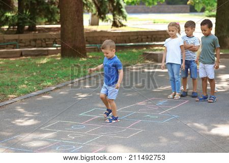 Little children playing hopscotch, outdoors