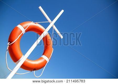 A bright orange life ring hangs on a white cross against the blue cloudless sky.