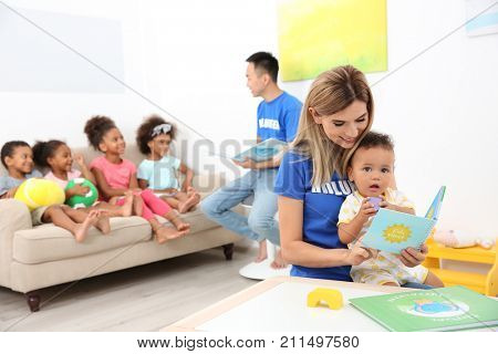 Young female volunteer reading book to little baby in light room. Volunteering abroad concept