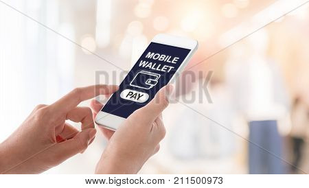 Woman hands holding and using smartphone with mobile wallet screen wallet icon and pay button on blurred shopping mall background. Mobile payment concept.