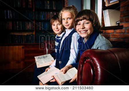 Three joyful children in school clothes sitting on a sofa and reading books. School fashion. Educational concept.