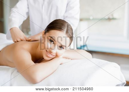 Happy girl enjoying massage of her back in dayspa salon