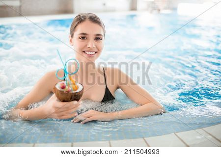 Smiling girl with cocktail enjoying day spa in warm water of whirlpool