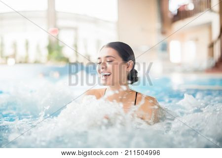 Excited female laughing while splashing warm water during spa procedure in whirlpool