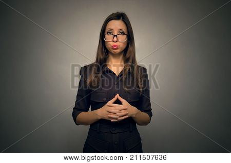 Portrait of young caucasian girl with long brown hair in glasses and strict dress isolated on gray background. Student girl. Secretary.