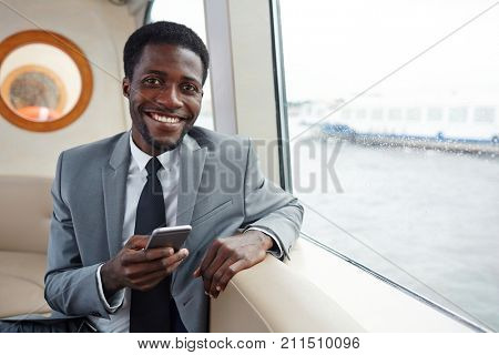 Waist-up portrait of cheerful African American white collar worker posing for photography while sitting at middle deck and browsing Internet on smartphone