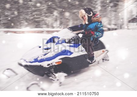 Boy driving snowmobile in a winter landscape