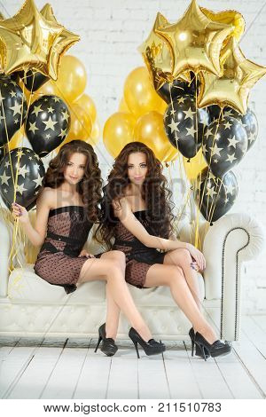 Girls twins sisters with updo hair at a partyon the background of golden balloons and stars. Women at the birthday party