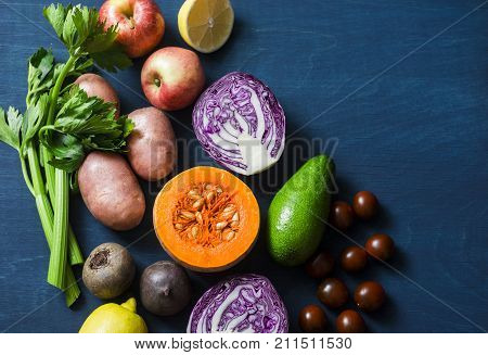 Healthy food vegetables background. Pumpkin red cabbage avocado red onions kumato tomatoes celery apples potatoes beets on a blue background top view. Vegetarian food set
